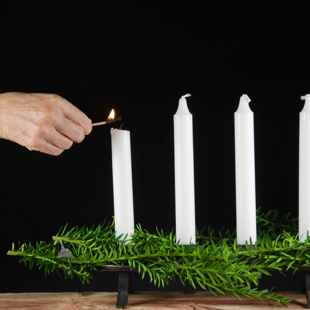 """Lighting the first advent candle"" stock image"