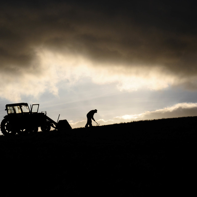 """Silhouette of farmer working next to his tractor up high in the clouds"" stock image"