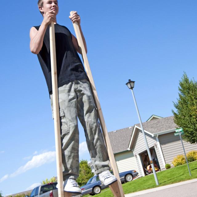 """Teenager balancing on stilts"" stock image"