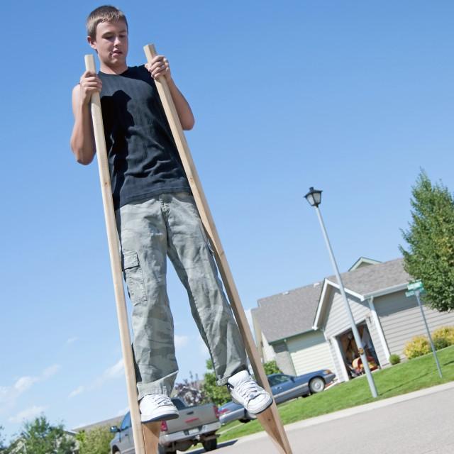 """Teenage boy on stilts"" stock image"