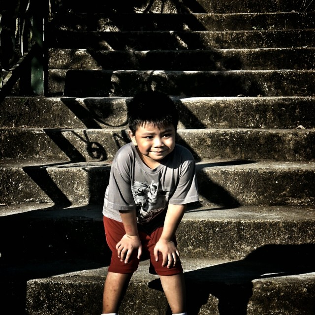 """little boy standing at bottom of stairs"" stock image"