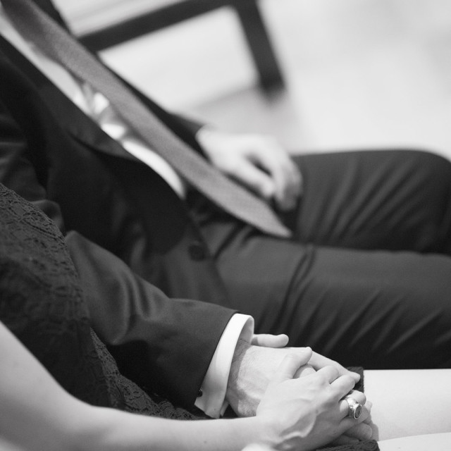 """""""Wedding guests sitting holding hands man and woman"""" stock image"""