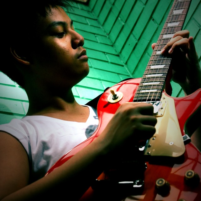 """young teenager playing an electric guitar"" stock image"