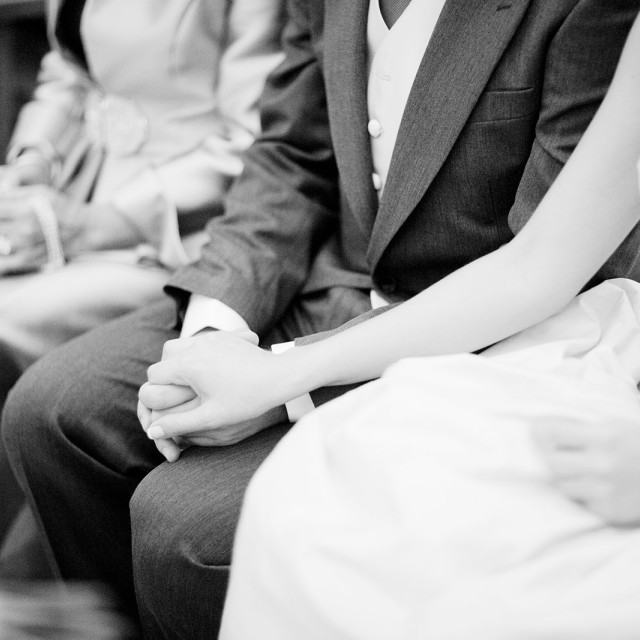 """""""Bridegroom and bride hold hands in wedding marriage ceremony bw"""" stock image"""