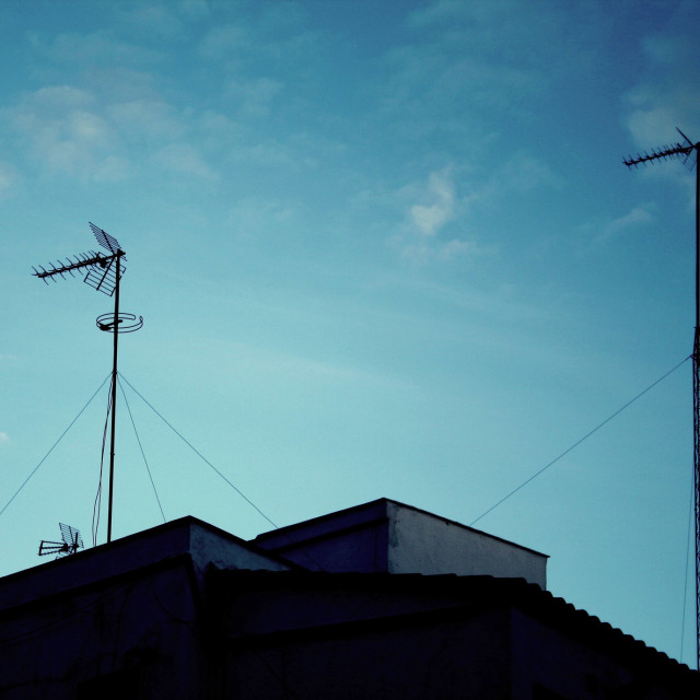 """TV arial antenna on roof of building and blue sky RF Stock Image silhouette"" stock image"