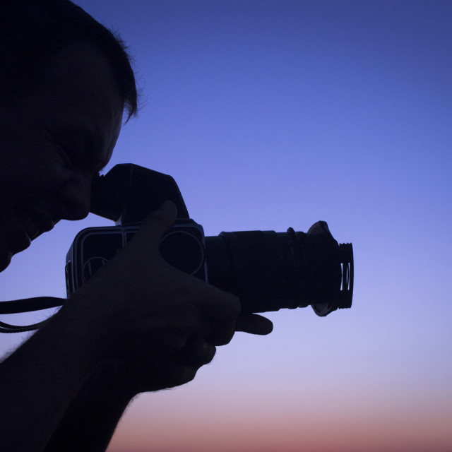 """Photographer taking photo in silhouette against blue purple sky rf Stock Image"" stock image"