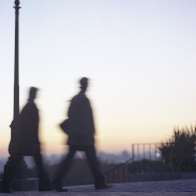"""Two people walking silhouette dusk sunset sky motion blur"" stock image"
