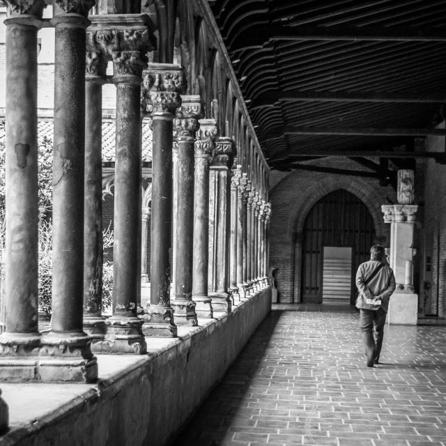 """Man Walking Through Cloisters in Toulouse B&W"" stock image"