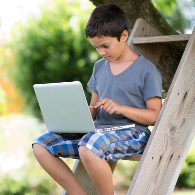 """Child playing on the computer with headphones outdoor"" stock image"