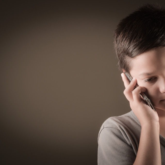 """Studio Shot Of French Boy With Mobile Phone"" stock image"