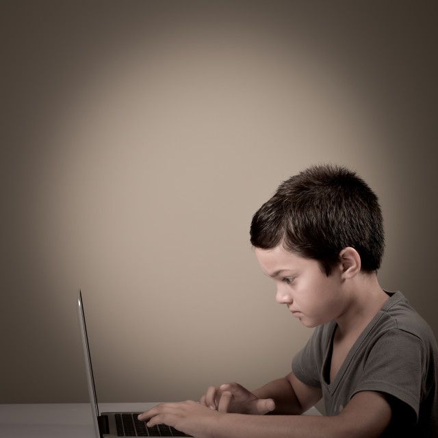 """""""Little boy concentrated playing whith a computer"""" stock image"""