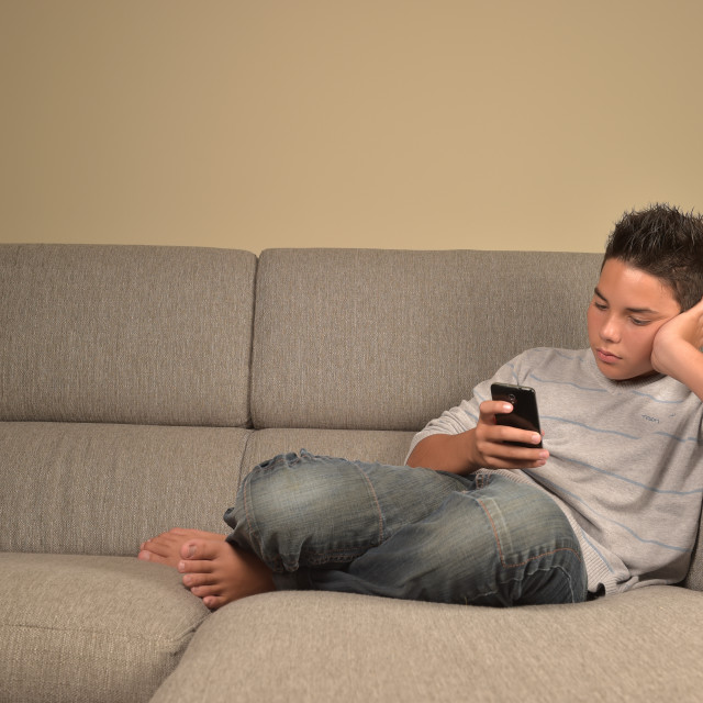 """""""Teenage boy with phone at home lying on a sofa"""" stock image"""