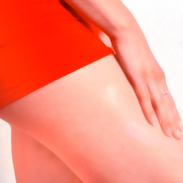 """Young woman applying cream on leg"" stock image"
