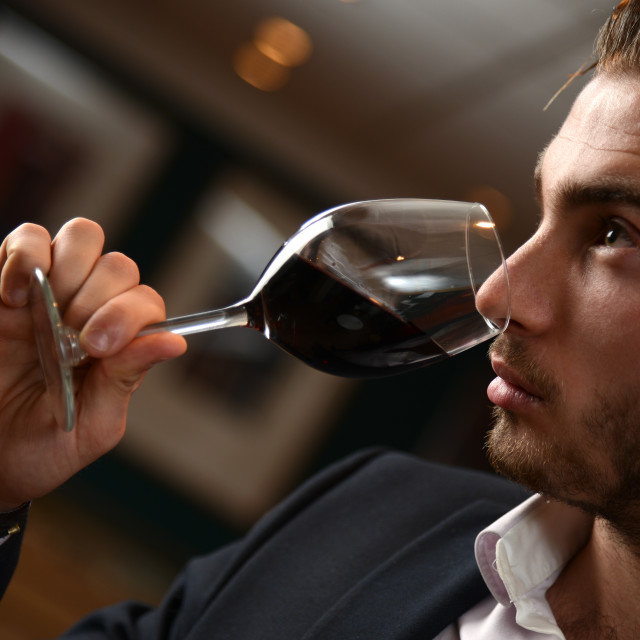 """Young man with redwine glasses at celebration or party"" stock image"