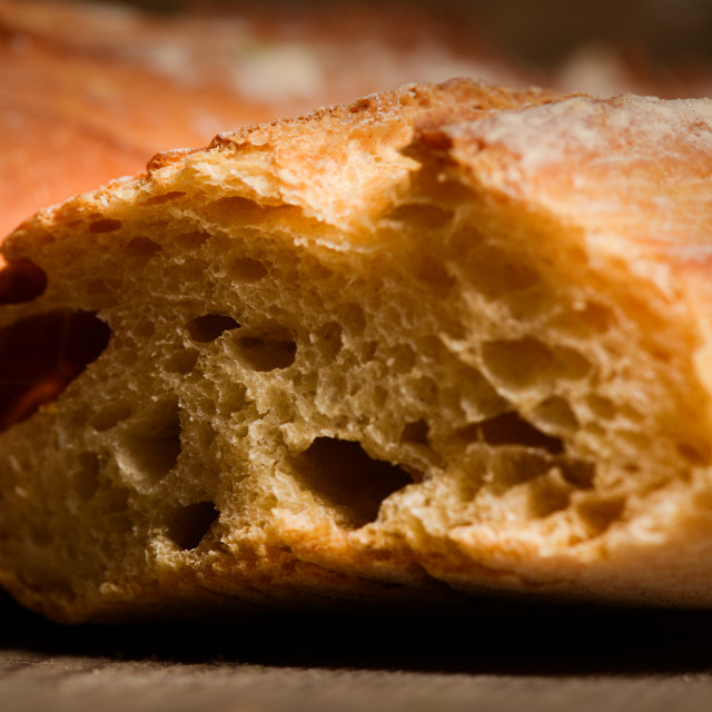 """French crusty bread, isolated on a wooden plank background"" stock image"