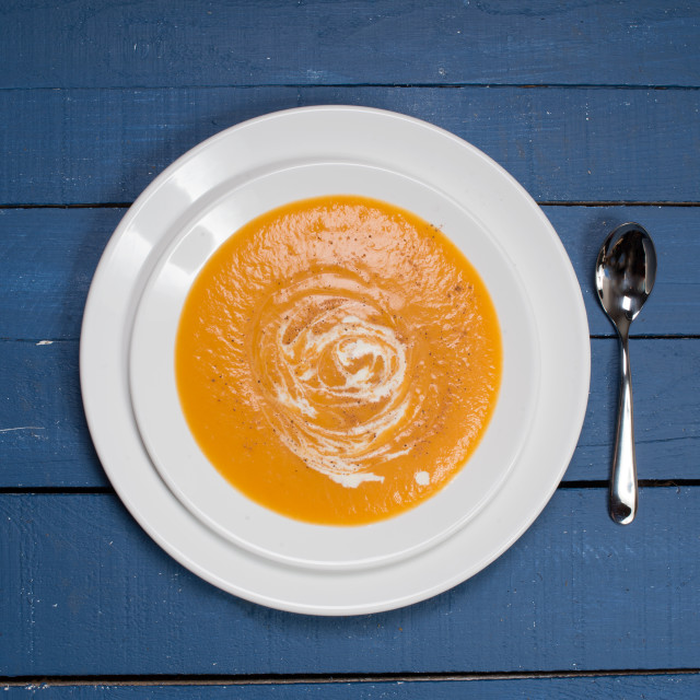 """""""plate of pumpkin soup on a blue wooden table"""" stock image"""