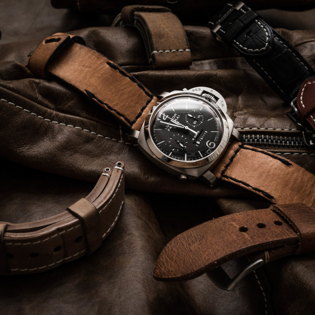 """A Panerai wristwatch amongst leather straps"" stock image"