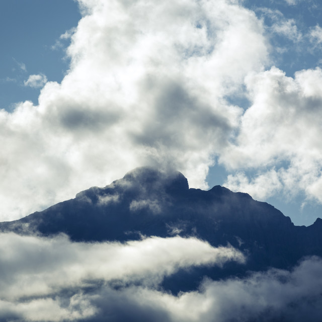 """Clouds around mountain ridge"" stock image"