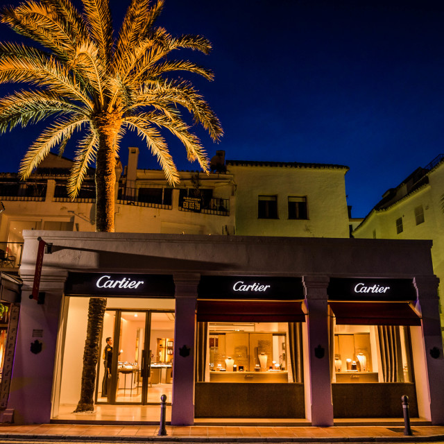 """""""A boutique in the shadow of a beautifully lit Palm Tree"""" stock image"""