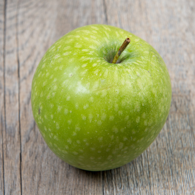 """green apple placed on a wooden table"" stock image"