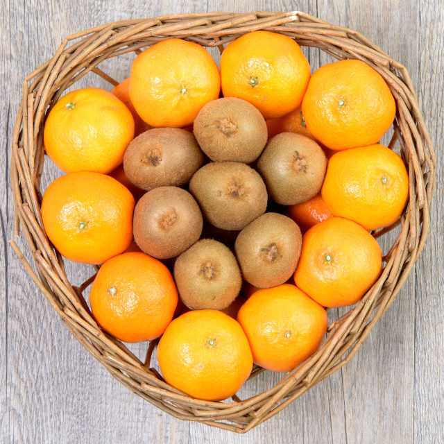 """""""tangerins and kiwi fruit in a wicker basket"""" stock image"""