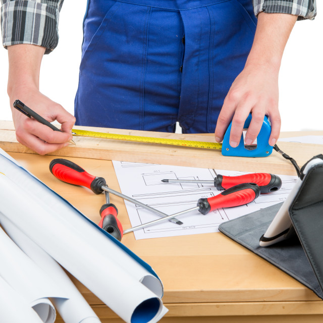 """""""a worker measuring a board with a tape measure"""" stock image"""