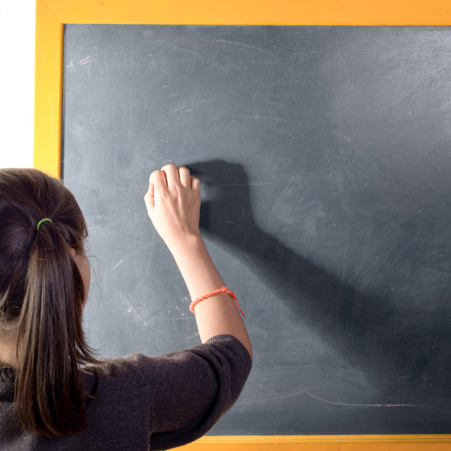 """a little girl with pigtails writes on a blackboard"" stock image"