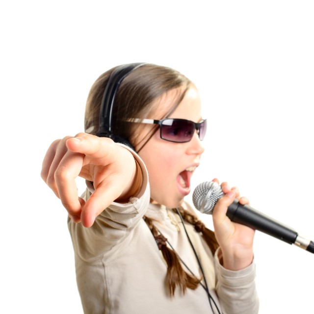"""a young girl with headphones singing with a microphone"" stock image"