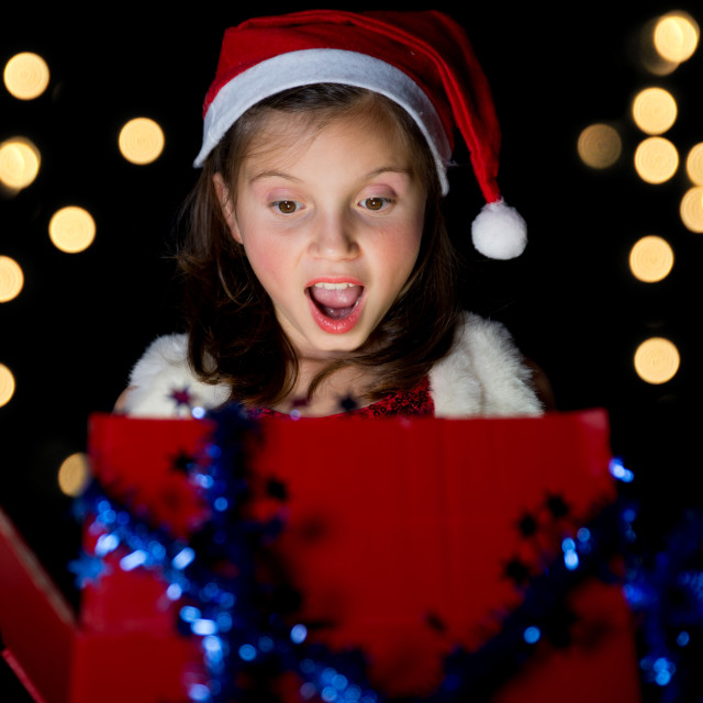 """a pretty little girl opens her Christmas present"" stock image"