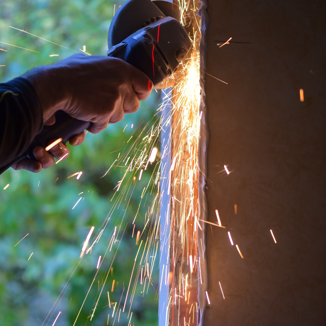 """Window renovation-Metal grinding with orange flying sparks"" stock image"