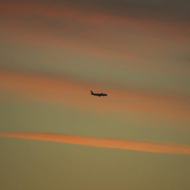 """Airplane in sky with clouds sunset evening colors"" stock image"