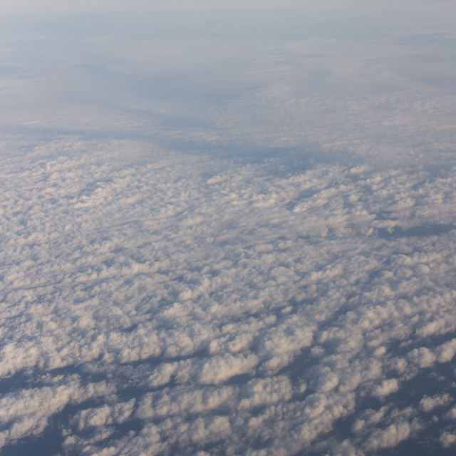 """Blue sky with clouds seen from plane window"" stock image"