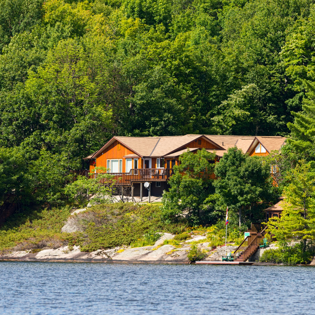 """Cottage on a rocky shore"" stock image"
