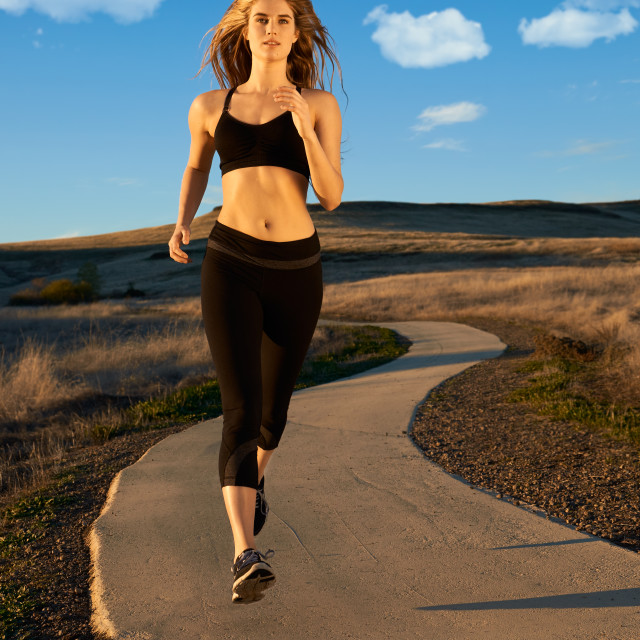 """Young Woman Running on an Outdoor Jogging Path."" stock image"