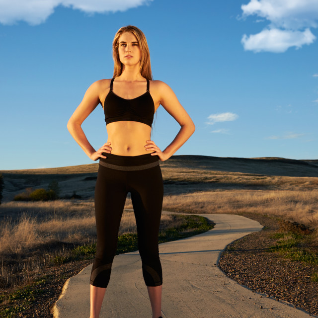 """Female Jogger Resting on a Running Trail"" stock image"