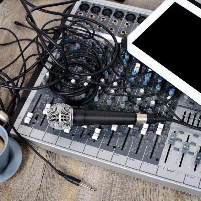 """""""digital tablet placed on a audio mixer with a coffee"""" stock image"""