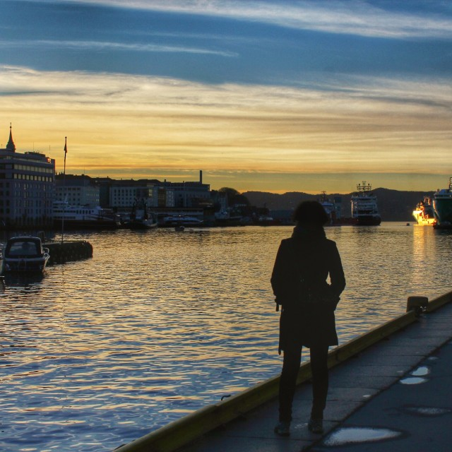 """""""Urban life in Norway, a woman watching the sunset over Bergen harbor"""" stock image"""