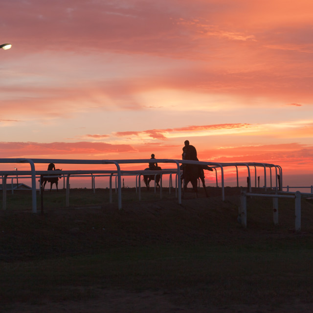"""Horses Riders Silhoutted Sunrise"" stock image"