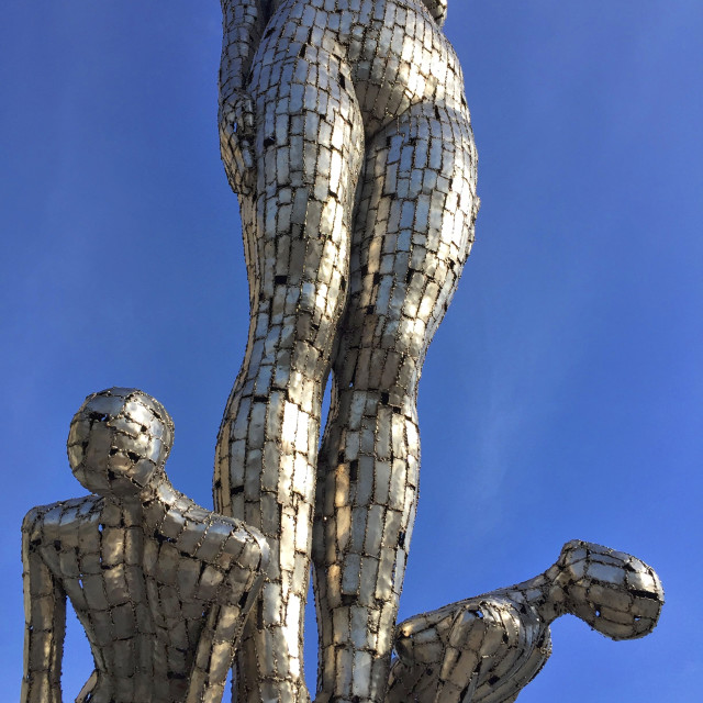 """Chrome statues looking up to the sky"" stock image"