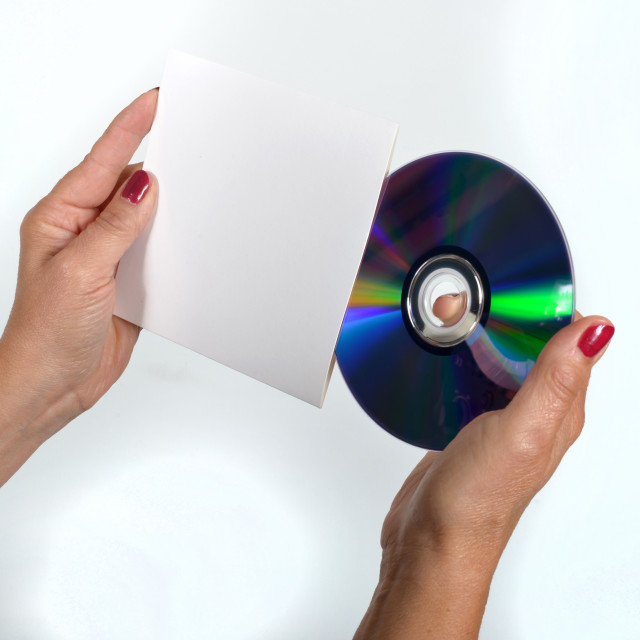 """""""Young woman liking a CD-ROM and its dress handkerchief"""" stock image"""