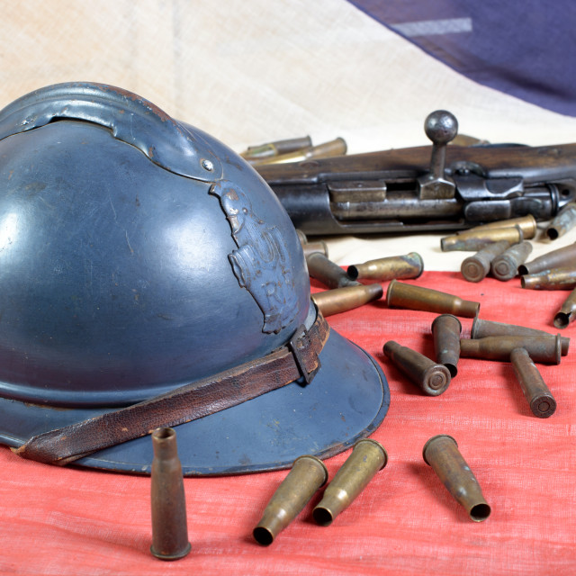 """french helmet of the First World War with a gun on a blue white red flag"" stock image"