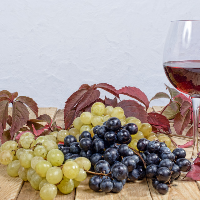 """""""glass of red wine with many bunches of grapes"""" stock image"""