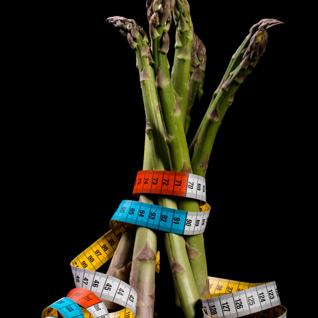 """Bundle of raw asparagus against black background"" stock image"