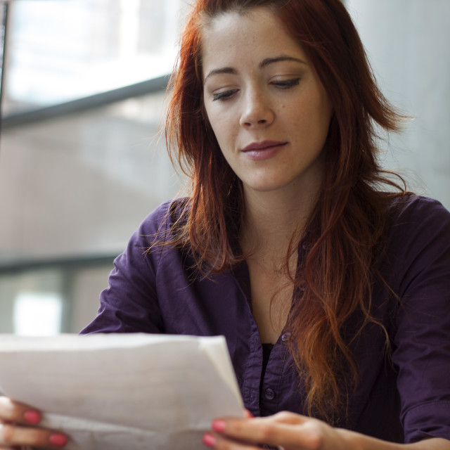 """""""businesswoman reading over financial documents - smiling"""" stock image"""