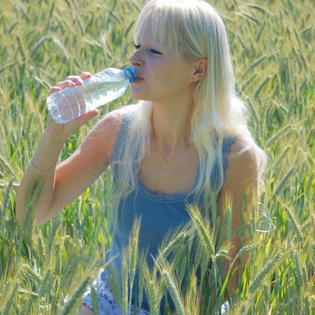 """Blond woman in field"" stock image"