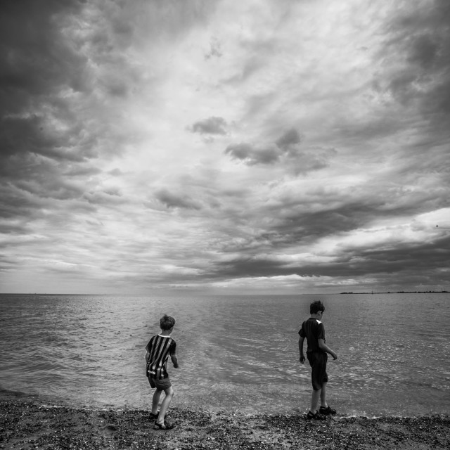 """Boys skimming stones"" stock image"