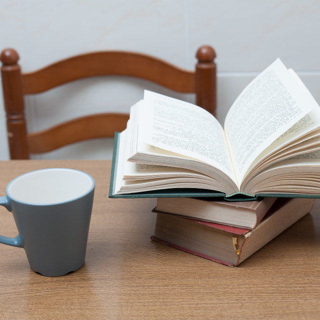 """""""Some books and a cup of milk or coffe on a table"""" stock image"""