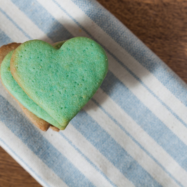 """Green butter cookies, heart shaped, on a striped fabric napkin"" stock image"