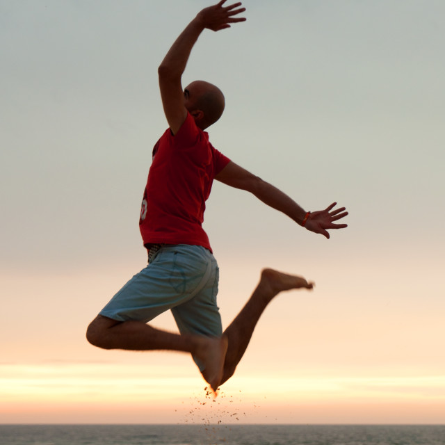 """Young man jumping at the beach at sunset. Joyful and funny vacations"" stock image"