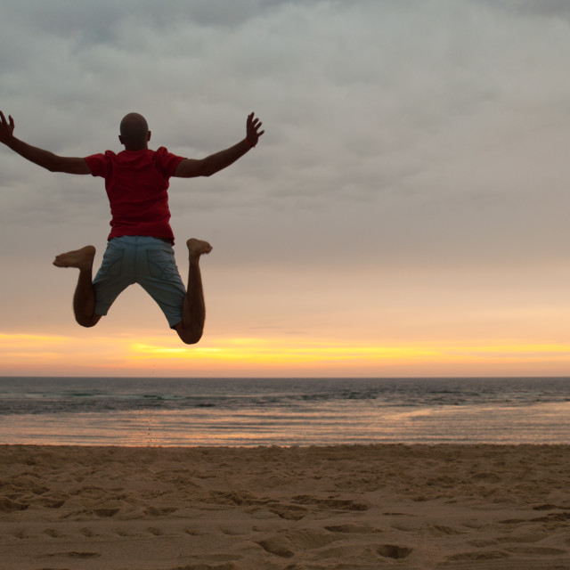 """""""Man jumping in the beach at sunset"""" stock image"""